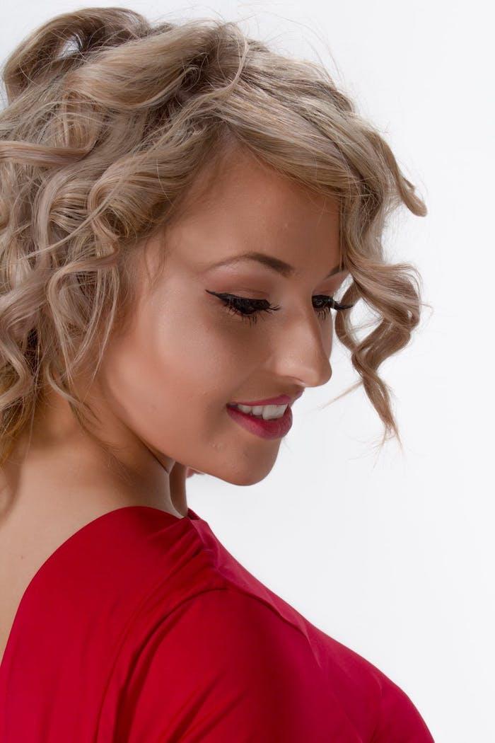 Haarfarbe Aschblond, schwarzer Lidstrich und roter Lippenstift, rote Bluse mit langen Ärmeln