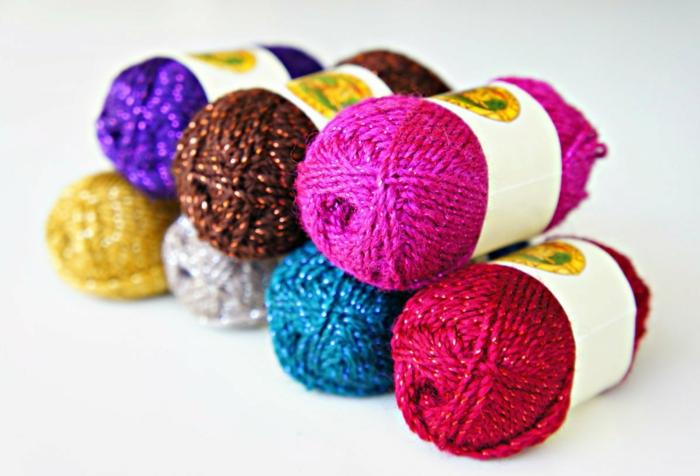 buntes Garn mit glätzenden Motiven, Bommel basteln in der Farben vom Regenbogen
