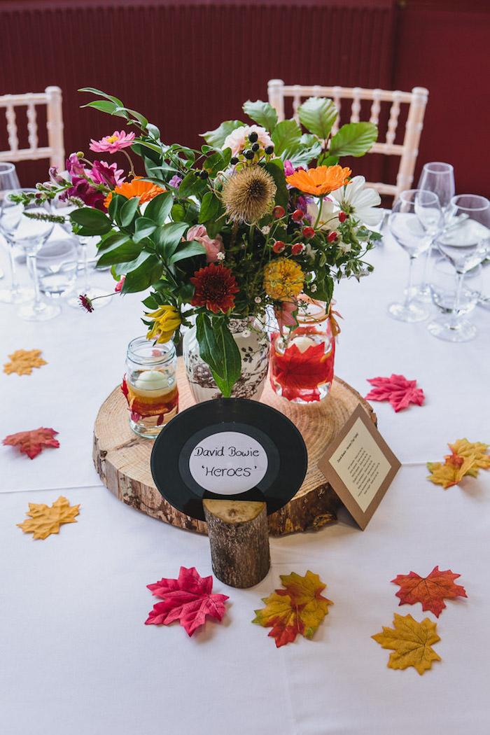 Tischdeko für herbstliche Hochzeit, rote und gelbe Herbstblätter auf dem Tisch, großer Strauß aus bunten Herbstblumen