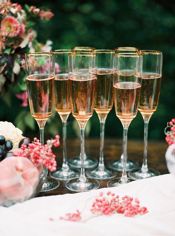 Champagner Gläser aus Kristall mit goldenem Rand, Schüssel voll mit Früchten
