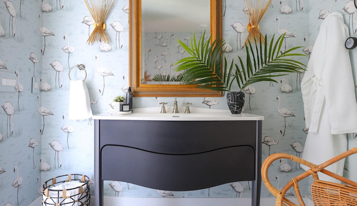 ein spiegel aus hoz und eine blaue flamingo tapete mit vielen kleinen weißen flamingos, ein badezimmer einrichten mit einer kleinen schwarzen vase mit grünen pflanzen