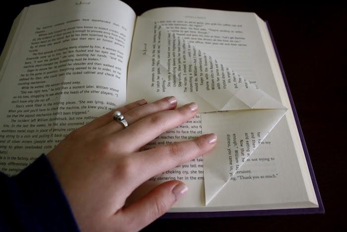ein buch mit einer gefalteten weien seite mit schwarzen buchstaben, bücher falten anleitung, eine hand einer frau mit einem ring, basteln mit papier