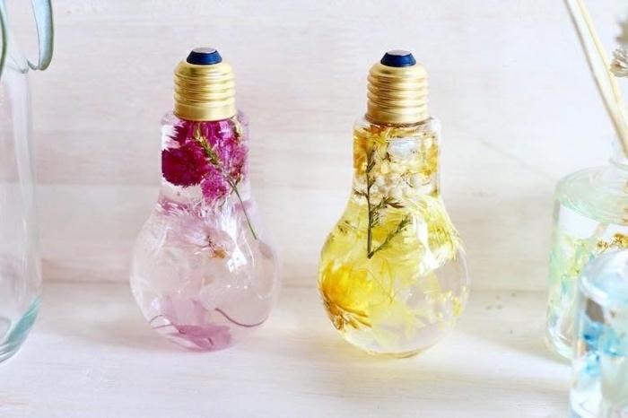 einfache bastelideen in glühbirnen, gelbe blumen und rosarote blumen in wasser in birnen stecken, kreative dekoidee