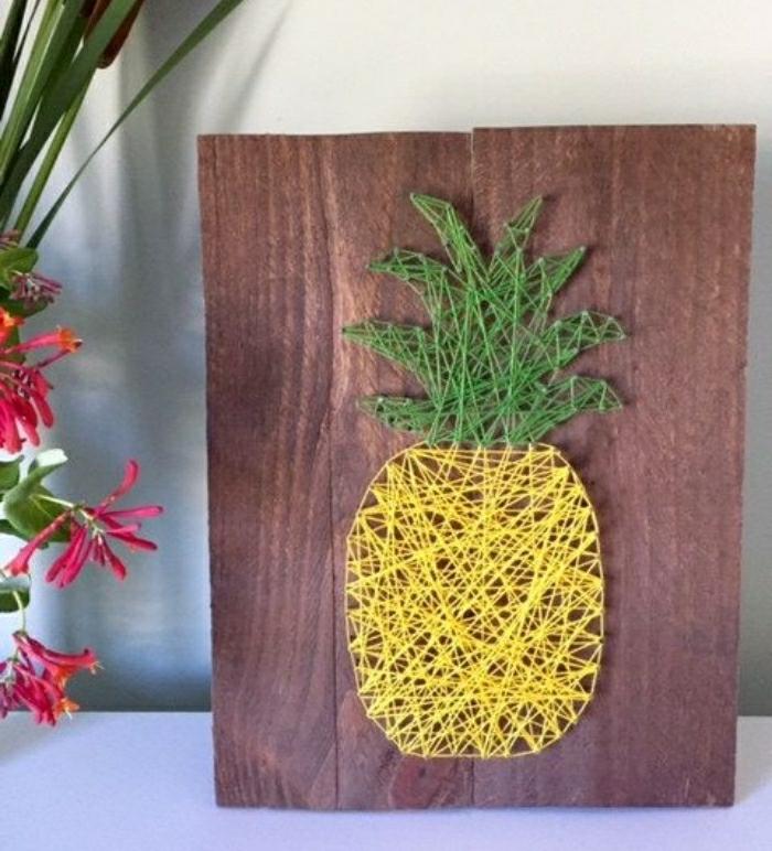 basteln mit kindern ananas wanddeko selber machen, gelbe und grüne faden, holzplatte als grund