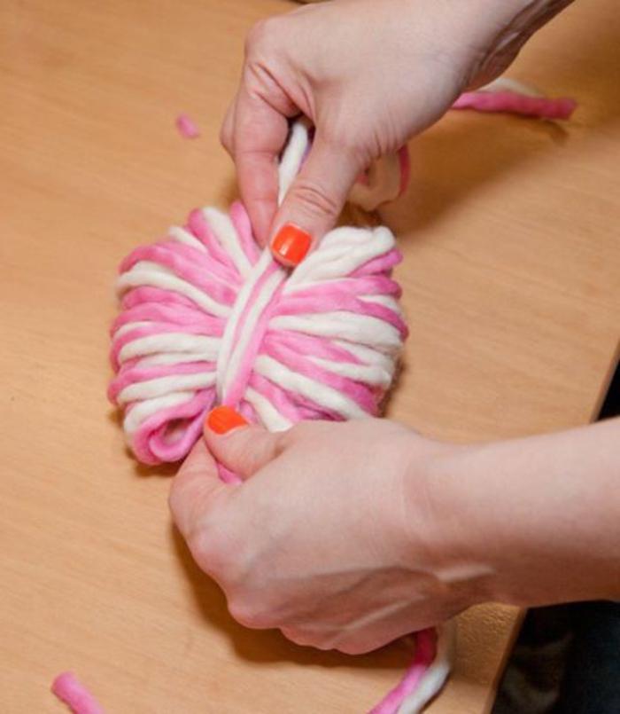 Schritt drei, rosa und weißer Pompon mit Faden bedecken, Pompons basteln