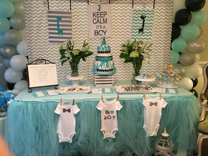 Babyparty Junge, eine Aufschrift Keep calm its a boy, eine blaue Torte und Klamottchen