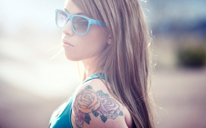 eine junge frau mkt einem blauen unterhemd und blaue brille, eine hand mit einem rosen tattoo mit zwei roten blumen und grünen blättern, tattoo frauen