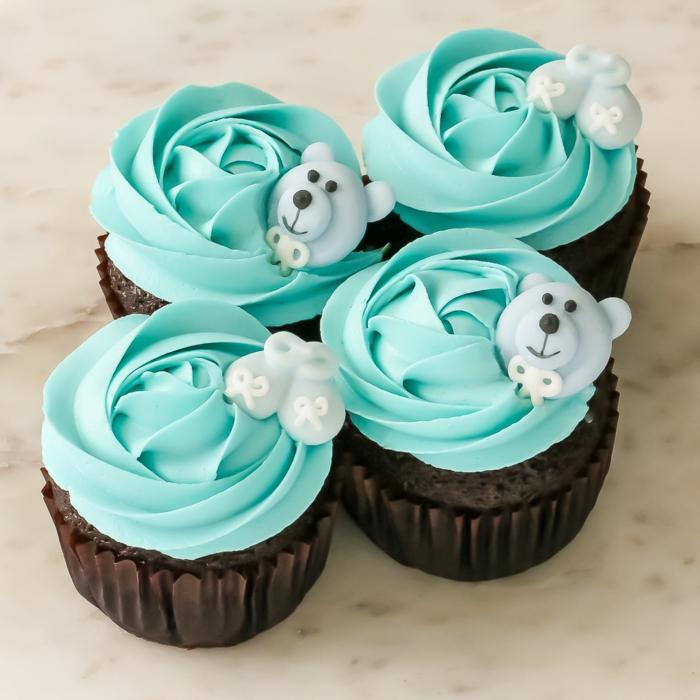 blaue Cupcakes mit Bären und kleine Schuhchen, Babyparty Ideen, etwas Süßes zum Naschen