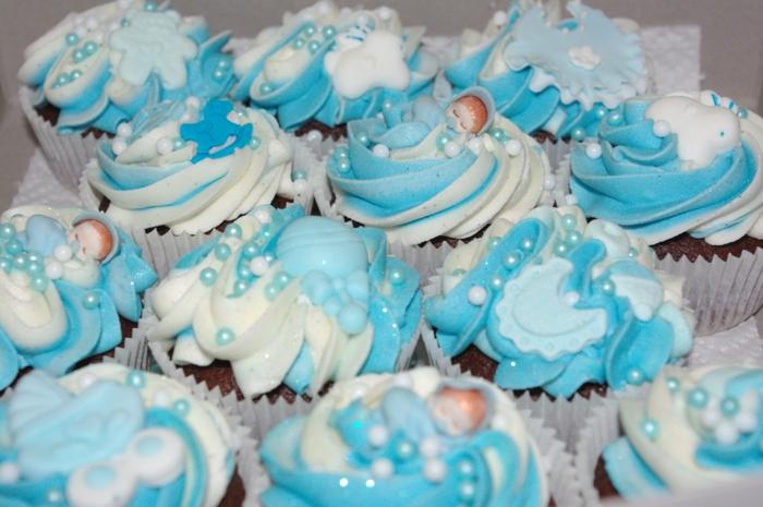 eine Menge Cupcakes mit kleinen schlaffenden Babyfiguren als Dekoration, Perlen, Babyparty organisieren