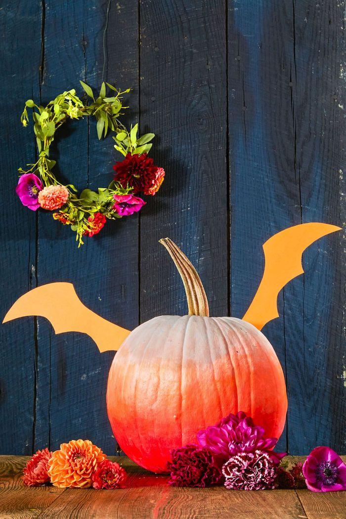 eine blaue wand aus blauen holzbrettern, eine orange fledermaus basteln aus einem kleinen orangen halloween kürbis mit orangen flügeln aus papier, orange und violette blumen und ein kranz