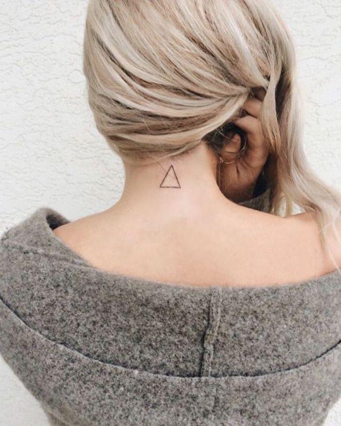 tattoo rücken frauen, eine weiße wand und eine junge frau mit einem kleinen rücken tattoo mit dreiecke, frauen tattoos ideen