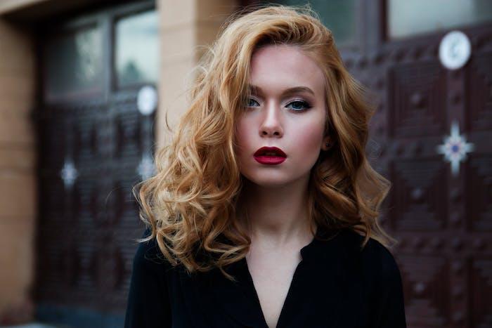 Mittellange blonde Haare mit Seitenscheitel, roter Lippenstift, schwarzes Top mit V-Ausschnitt