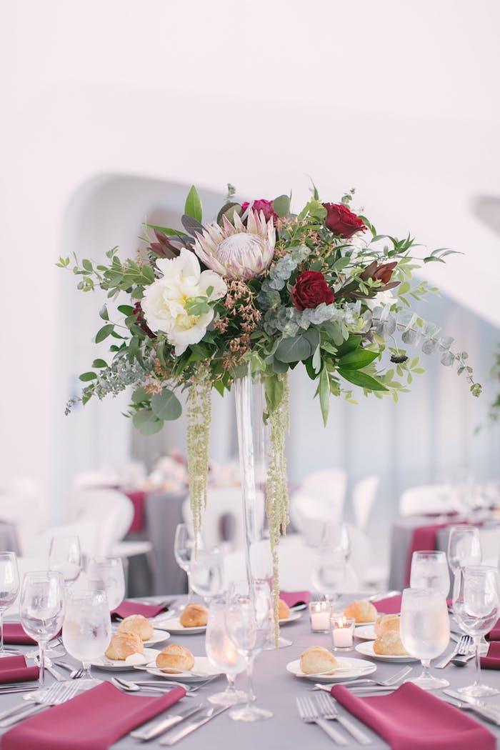 Großer Blumenstrauß in Kristallvase, dekoriert mit Perlen, graue Decke und rote Servietten