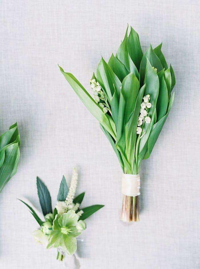 Kleine Sträuße aus Maiglöckchen mit weißem Band und Perlen dekoriert
