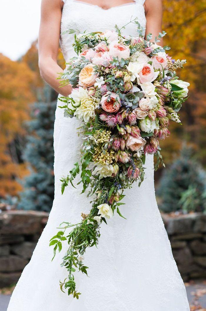 ein garten und grünen blättern, eine junge braut mit einem langen weißen brautkleid und mit einem brautstrauß mit vielen pinken, roten und gelben rosen und grünen kleinen blättern