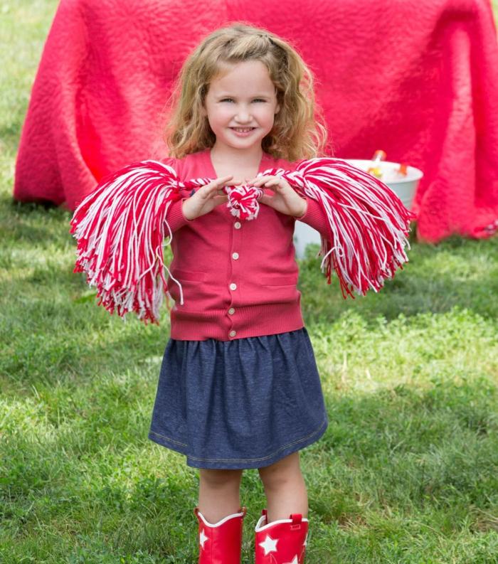 DIY Cheerleader Pompons von einer kleinen Prinzessin mit blondem Haar, Pompons in weißer und roter Farbe