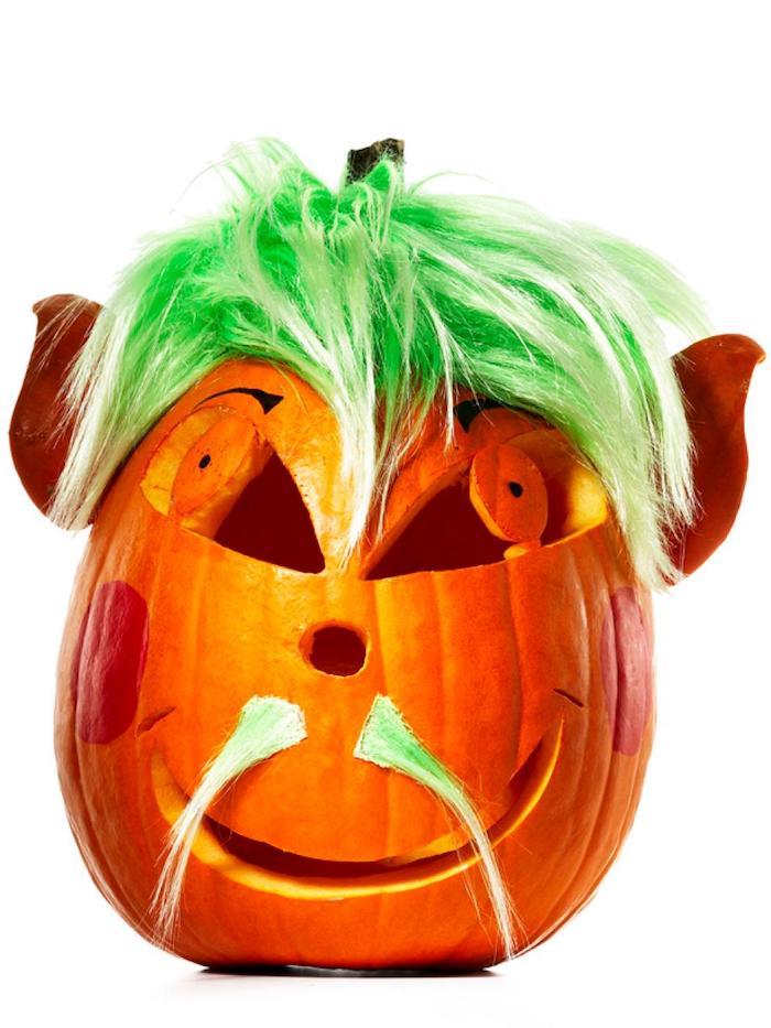 ein oranger halloween kürbis mit einem grünen haar und schnurrbart und großen orangen augen, halloween kürbis schnitzen, lustige kürbisgesichter schnitzen