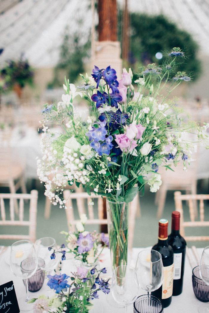 Schöner Strauß aus Feldblumen in Glsvase, simple Tischdeko, weiße Tischdecke