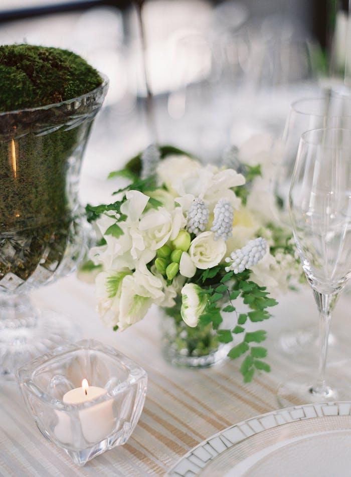 Stilvolle Tischdeko für Hochzeit, weiße Blumen und kleine Duftkerzen, Moos in Vase