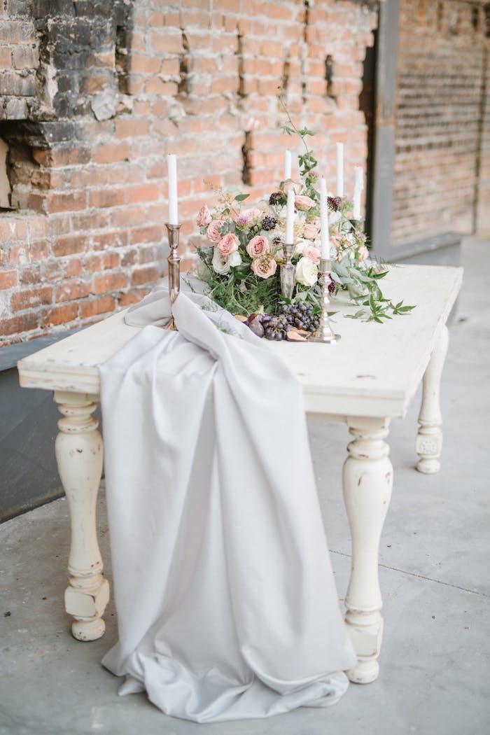 Idee für Tischdeko in Landhausstil, weißer Tisch mit Altersspuren, viele Blumen und weiße Kerzen