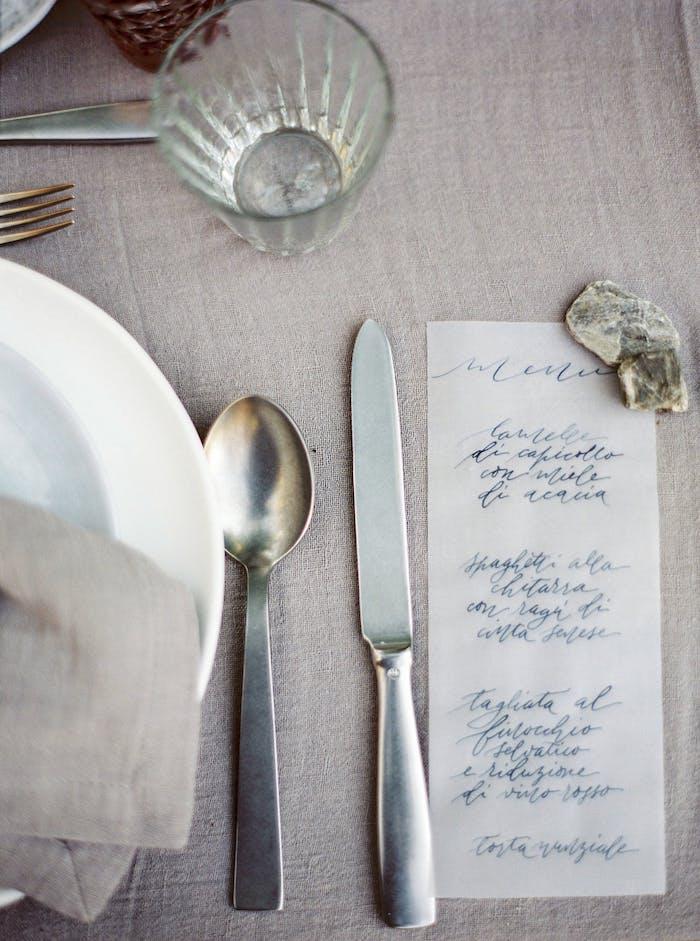 Originelle und kreative Ideen für Tischdeko, handgemachtes Menü, kleines Steinchen, graue Tischdecke