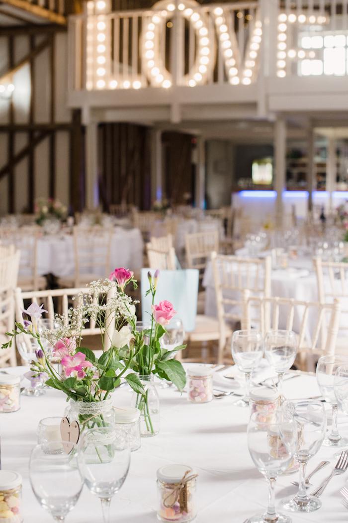 Schlichte und stilvolle Tischdeko, Vasen aus Einmachgläsern mit Spitze dekoriert, rosafarbene Feldblumen