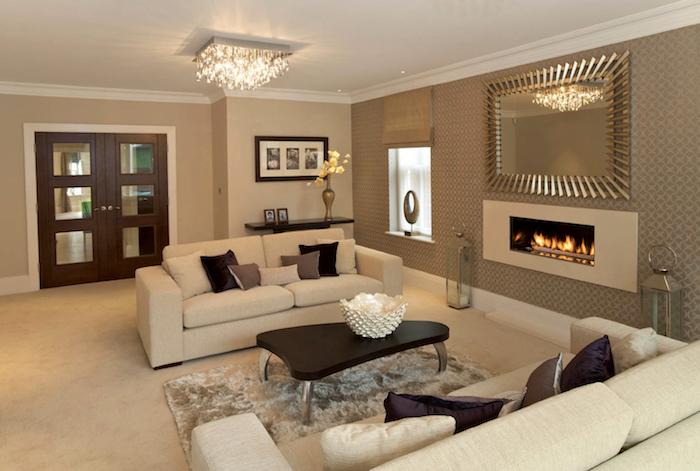 deko ideen wand, hängeleuchte aus kristall, zwei sofas mit braunen dekokissen, kamin, großes spiegel