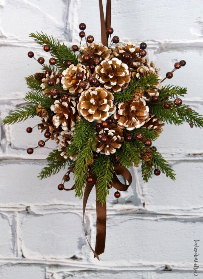 eine weiße tür und ein kranz mit vielen grünen ästen und mit einer braunen schleife und vielenn braunen tannenzapfen, einen kranz selber basteln, weihnachtsdeko