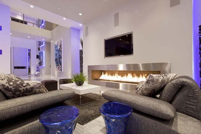 dekoideen wohnzimmer, großes langes kamin, blaues led licht, blaue hocker