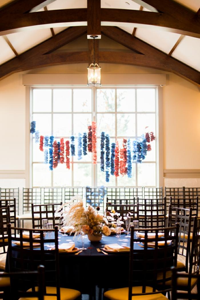 Babyparty organisieren, hängende Papiere am Fenster, Blumen in der Mitte des Tisches