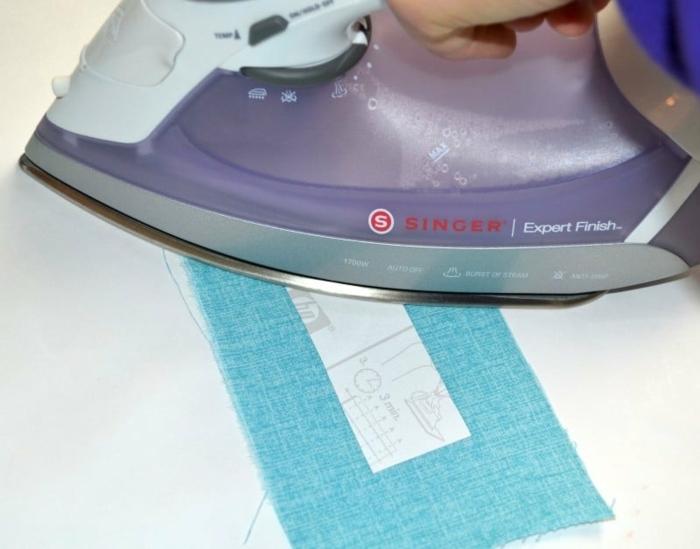 Bügeleisen, Stück Stoff in blauer Farbe, Lesezeichen nähen und mit Bildern verschönern