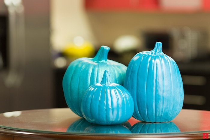 ein kleiner tisch und drei kleine bemalte blaue halloween deko kürbisse, halloween deko selber basteln