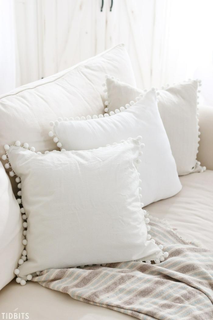 Sofa in weißer Farbe, drei Kissen mit weißen Pompons verziert, Pompons selber machen
