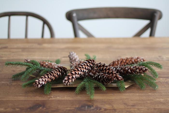 ein brauner tisch aus holz und eine weiße wand und zwei stühle aus holz, einen adventskranz selber machen aus grünen ästen und aus langen braunen tannenzapfen, basteln mit tannenzapfen