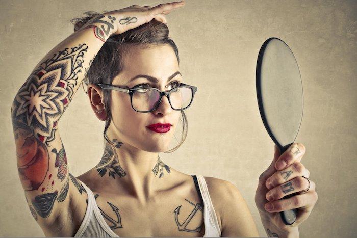 eine junge frau mit roten lipppen und einem kleinen schwarzen spiegel und einem weißen unterhemd, ein anker brust tattoo frau