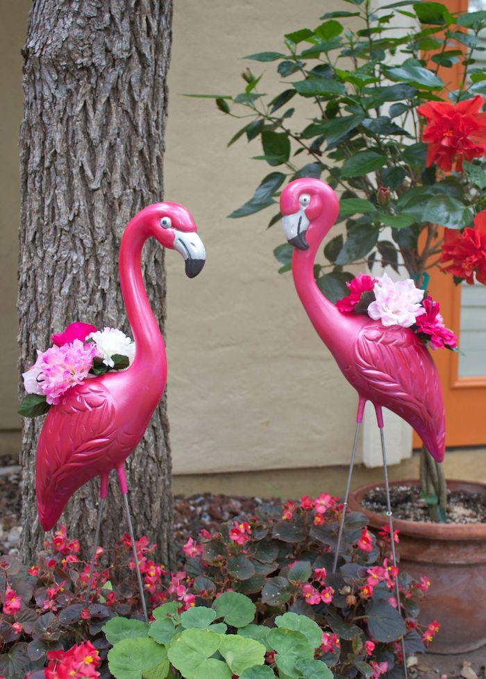 ein garten mit einem baum und mit zwei dekorativen pinken flamingos mit weißen und violetten blumen mit grünen blättern, flamongo deko, rote blumen und ein haus