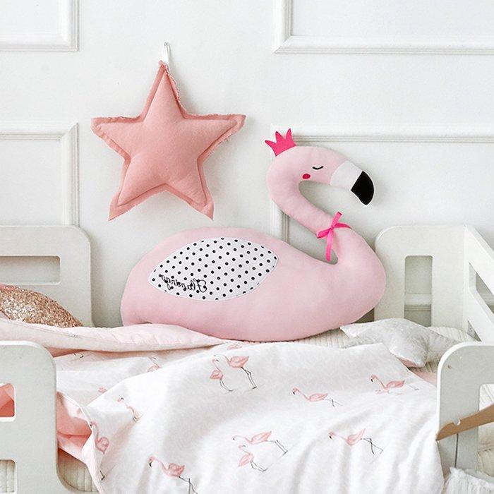 ein kinderzimmer einrichten, flamingo deko, eine pinke große flamingo mit einer violetten krone und ein stern und ein weißes bett mit einer weißen decke mit kleinen pinken flamingos