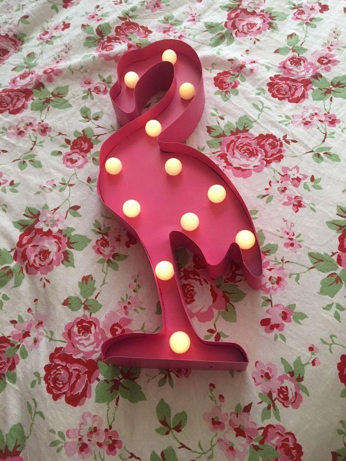 eine pinke flamingo mit vielen kleinen gelben leuchten, flamingo bilder, ein bett mit einer weißen decke mit roten rosen