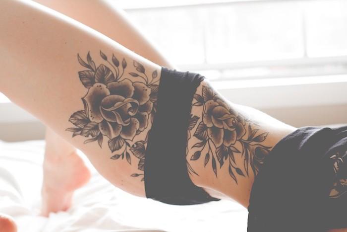 eine frau und ein bett, eine junge frau mkt einem großen schwarzen tattoo mit schwarzen rosen und mit schwarzen blättern, frauen tattoos