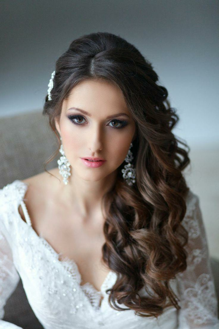 eine schöne Braut mit lockigem Haar, lange Ohrringe, lässige Locken und Haarschmuck