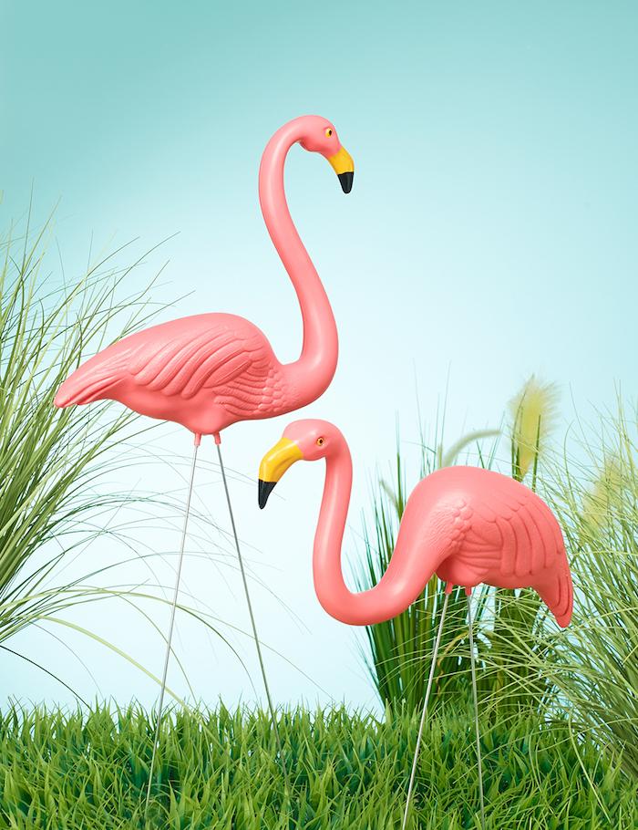 ein blauer himmel und grüne pflanzen, ein garten mit flamingo deko, zwei pinke große flamingos