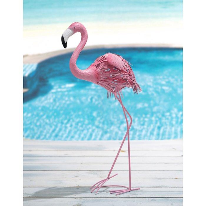 ein boden aus holz und ein schwimmpool und eine pinke flamingo mit kleinen schwarzen augen, flamingo deko
