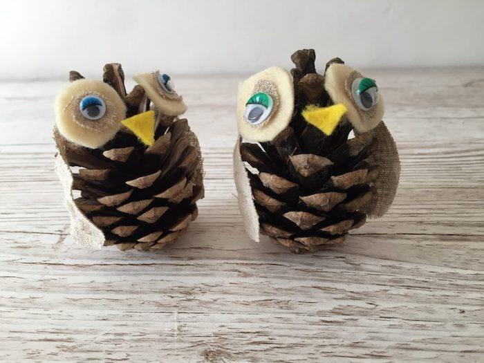 eulen basteln aus tannenzapfen, ein tisch aus holz und zwei kleine vögel aus braunen kleinen tannenzapfen und mit blauen und grünen augen, basteln mit tannenzapfen