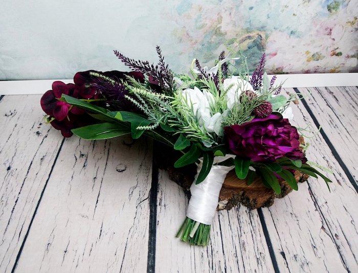 ein weißer boden aus holz und ein kleiner brautstrauß mit vielen weißen rosen und violetten blumen und grünen blättern