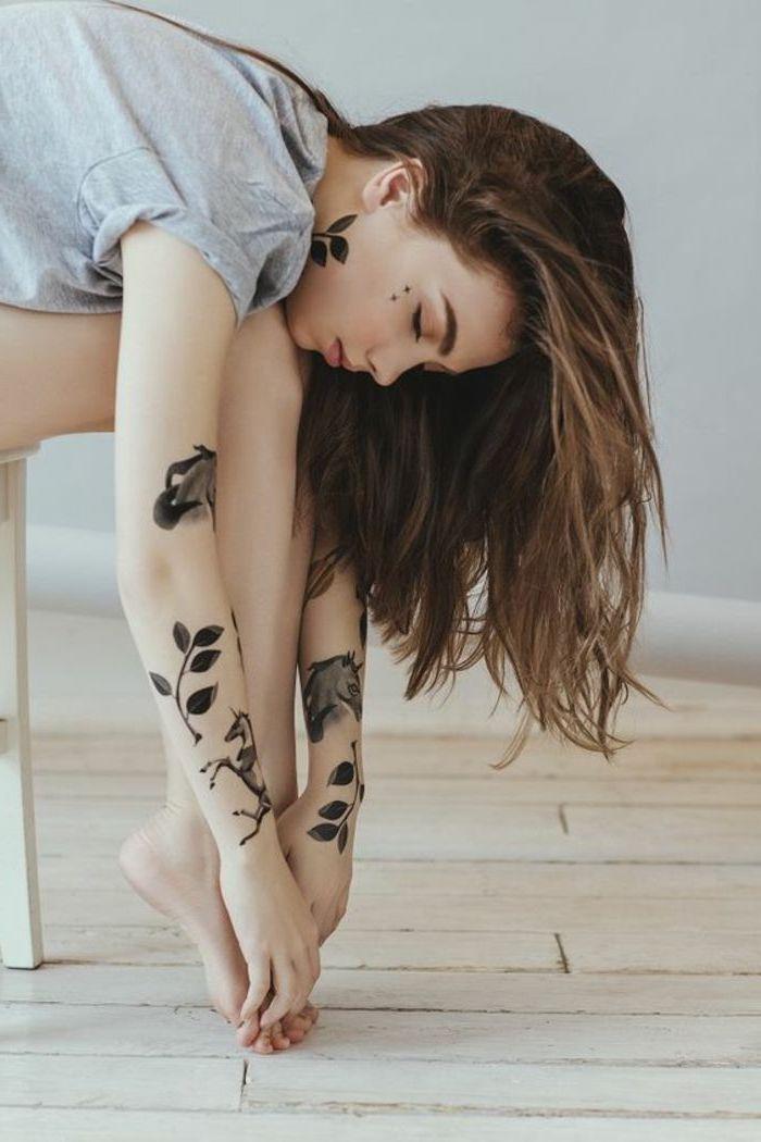 junge frau mit händen mit großen schwarzen tattoos mit zwei schwarzen einhornern mit dichten mähnen und schwarzen blättern, ein boden aus holz, tattoos für frauen