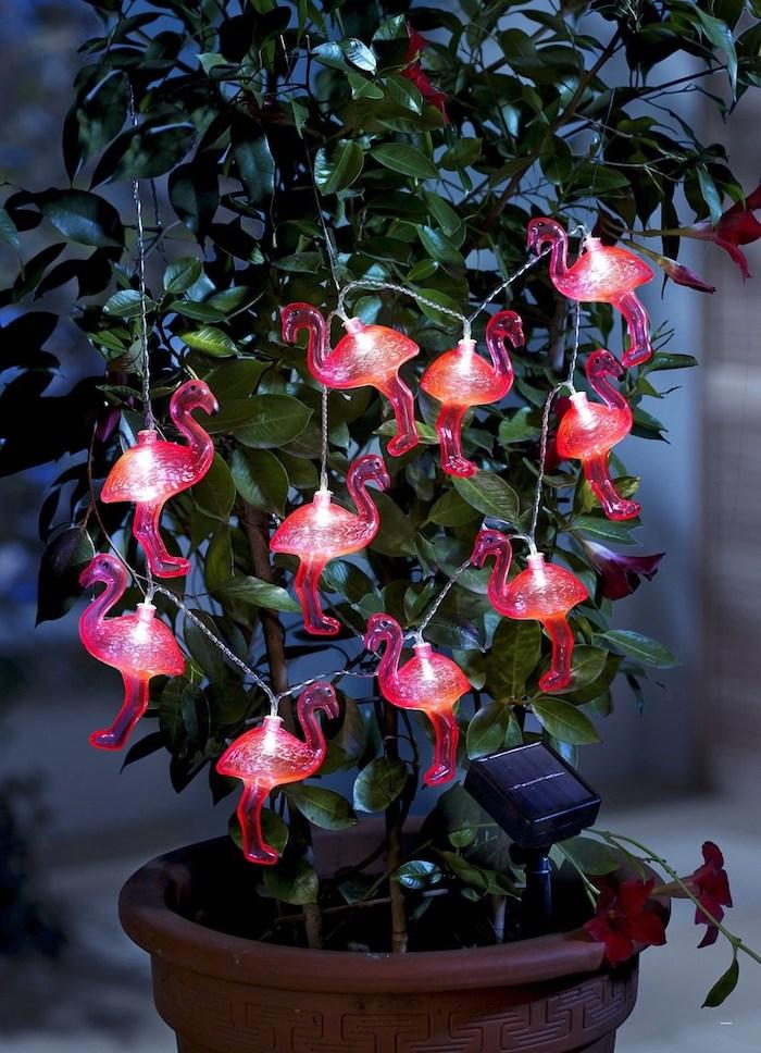 ein brauner blumentopf mit einer grünen pflanze mit grünen blättern und mit vielen kleinen pinken flamingos mit kleinen leuchten, flamingo deko