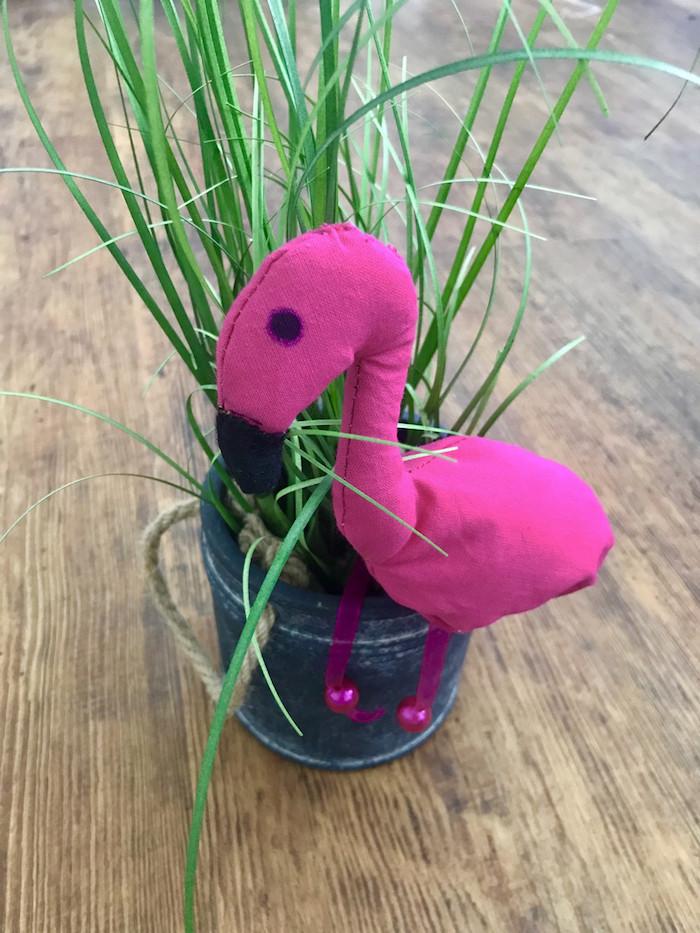 ein blumentopf mit einer grünen pflanze und eine kleine violette dekorative flamingo und ein brauner boden aus holz