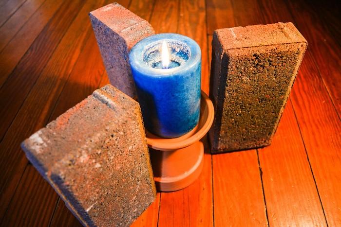 eine blaue kerze und ein blumentopf aus keramik, teelichtofen bauanleitung, drei braune ziegel und ein boden aus holz