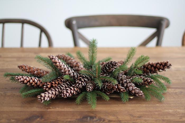 eine weiße wand und stühle aus holz und ein ein tisch aus holz, basteln mit tannenzapfen weihnachten, einen adventskranz selber machen aus braunen tannenzapfen und grünen ästen
