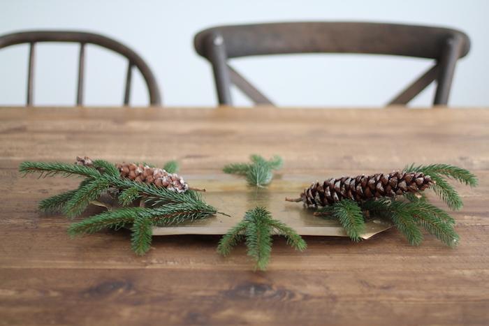 ein brauner tisch aus holz und eine weiße wand und zwei stühle aus holz, einen adventskranz selber machen aus grünen ästen und braunen tannenzapfen, tannenzapfen basteln